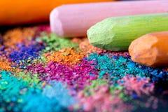 Migalhas do giz multi-colorido em um fundo preto Alegria, carnaval, panorama Um jogo para crianças Arte Fotografia de Stock Royalty Free