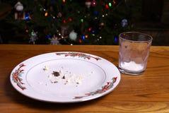 Migas de la galleta de la Navidad y vidrio de leche vacío imagen de archivo libre de regalías