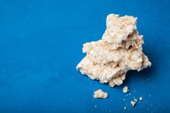Migas y restos de los bocados curruscantes del arroz dietético en un fondo azul, espacio vacío para el texto imagen de archivo libre de regalías