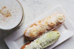 Migdałowi i pistacjowi eclairs i latte, odgórny widok zdjęcie stock