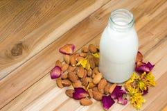 Migdału mleko w butelki szkle z migdałami na woodene tle w Zdjęcia Royalty Free