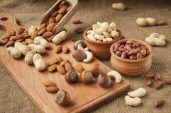 Migdały, nerkodrzewu arachid, hazelnuts w drewnianych pucharach na drewnianym i burlap, workowy tło Zdjęcie Royalty Free