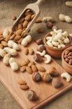 Migdały, nerkodrzewu arachid, hazelnuts w drewnianych pucharach na drewnianym i burlap, workowy tło Zdjęcie Stock
