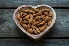 Migdały w drewniany serce kształtującym naczyniu zdjęcie stock