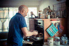 Miggle age man cooking. At home Stock Photos
