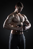 Mighty fitness man showing his gread body with dumbbells. In hand on black background Stock Photo