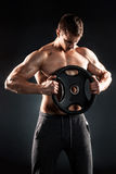 Mighty fitness man showing his gread body with dumbbells. In hand on black background Royalty Free Stock Photos