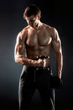 Mighty fitness man showing his gread body with dumbbells. In hand on black background Stock Image