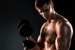 Mighty fitness man showing his gread body with dumbbells. In hand on black background Stock Images