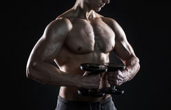 Mighty fitness man showing his gread body with dumbbells. In hand on black background. Close-up Royalty Free Stock Images