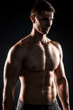 Mighty fitness man showing his gread body with dumbbells. In hand on black background. Close up Royalty Free Stock Image