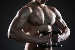 Mighty fitness man showing his gread body with dumbbells. In hand on black background. Close up Stock Photo