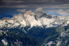 Mighty Jalovec and Mangart peaks and pine forests, Julian Alps Royalty Free Stock Photos