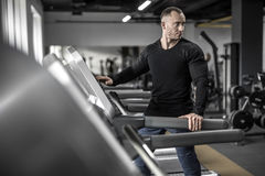 Mighty man on treadmill. Handsome muscular man is preparing to run on the treadmill in the gym. He wears a black sweatshirt and blue pants. Guy looks backward Royalty Free Stock Images