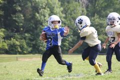 Mighty Mite player using a stiff arm. Royalty Free Stock Photos