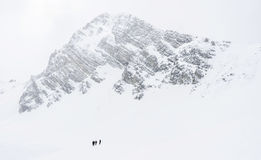 Winter Season in the Mountains. Scenic, cold winter landscape. Skiers in front of a big mountain, covered in snow Stock Images