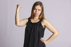 Mighty muscular woman. Stout pregnant woman posing in studio, photo on grey background Royalty Free Stock Photos