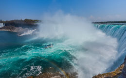Mighty Niagara River roars over the edge of the horseshoe falls in Niagara Falls Ontario.  Misty foggy spray rises up. Stock Image