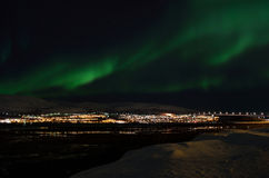 Mighty northern light dancing over snowy mountain peak in northern norway on the whale island settlement Stock Images