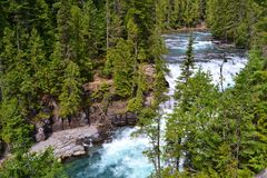 MIGHTY RIVER AND WATERFALL, GLACIER NATIONAL PARK Royalty Free Stock Photo