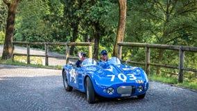 1000 Miglia 2018, Brescia - Italië 19 mei, 2018: Het historische Mille Miglia-autoras Twee mensen in een historische cabriolet bl stock foto's