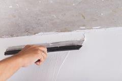 Miglioramento della Camera il lavoratore mette lo strato di finitura dello stucco sulla parete Fotografie Stock