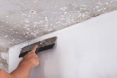 Miglioramento della Camera il lavoratore mette lo strato di finitura dello stucco sulla parete Fotografia Stock