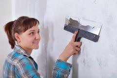 Miglioramento della Camera la lavoratrice mette lo stucco sulla parete Immagine Stock