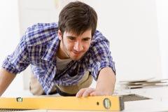 Miglioramento domestico delle mattonelle - tuttofare con il livello Fotografia Stock