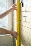 Miglioramento domestico - il tuttofare misura la rettitudine della parete Fotografie Stock Libere da Diritti