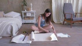 Miglioramento domestico, misure della giovane donna e carta da parati dei tagli per la riparazione la stanza sul pavimento in un  archivi video