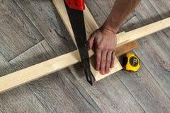 Miglioramento domestico, sega, legname e righello sul pavimento di legno Immagine Stock