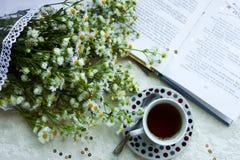Migliore mattina - tè, fiori e libro immagine stock