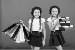 Migliore prezzo Buy ora Centro commerciale di visita Le ragazze dei bambini tengono i pacchetti dei sacchetti della spesa del maz fotografia stock