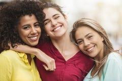 Migliori amici che abbracciano e che ridono sulla via immagine stock