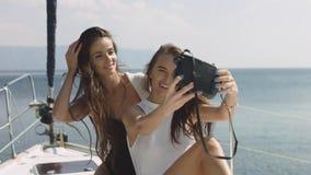Migliori amici che usando macchina fotografica e prendendo selfie sul selfie di lusso della barca a vela Immagine Stock