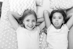 Migliori amici per sempre I bambini delle ragazze mettono sul letto con la vista superiore dei cuscini svegli Concetto del partit fotografie stock