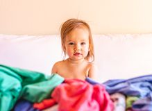 Mignon, adorable, souriant, b?b? caucasien s'asseyant dans une pile de blanchisserie sale sur le lit images stock