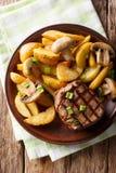 Mignon de prendedero jugoso con las cuñas y las setas fritas de la patata cerca Imagenes de archivo