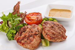 Mignon grilled on plate with garnish of vegetables and sauce. Stock Images