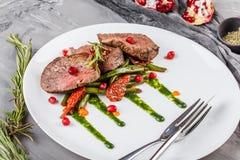 Mignon moyen juteux de filets de boeuf avec les haricots verts, la grenade et la sauce dans le plat sur le fond gris Parabolo?des photographie stock