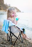 Mignon petite fille sur la plage buvant d'une tasse de jouet photographie stock libre de droits