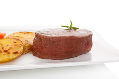 Mignon steak. Mignon steak with potatoes on white plate on white background, top view. Culinary steak eating royalty free stock photography