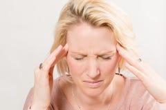 Migrändam Touches Sides av huvudet med fingerspetsar arkivfoto