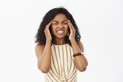 Migraine die me doden Portret van intense ontstemde jonge Afrikaanse Amerikaanse onderneemster die tanden van pijn dichtklemmen stock afbeelding