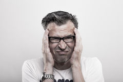 Migraine Headache. Man holds his hands to his temples royalty free stock image