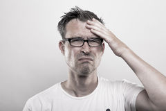 Migraine Headache. Man holds his hands to his temples royalty free stock photo