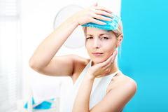 Migraine headache. The woman puts a cold compress to the head Royalty Free Stock Images