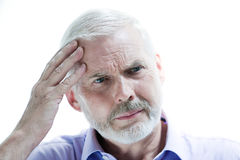 Migraine or memory loss illness senior man. Portrait on isolated withe background of a handsome expressive senior holding his head in hand headache memory loss Stock Photo