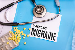 Migraine word written on medical blue folder with patient files. Pills and stethoscope on background stock image